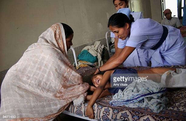 Nepali nurses and mother look after nineyearold Sunil Sharma in a hospital who was injured in an explosion ten days earlier by Maoist insurgents...