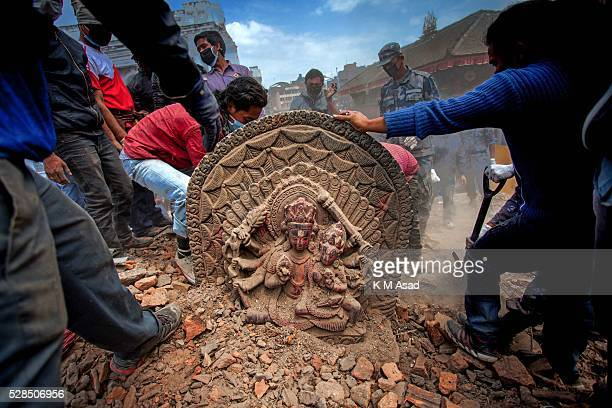 KATHMANDU BAKTOPUR KATHMANDU NEPAL Nepali people and soldiers try to recover a religious statue from the rubble in Darbar Square after a massive...