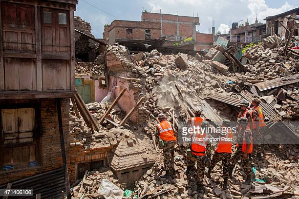 Nepali police look for two women buried in yesterday's aftershock.