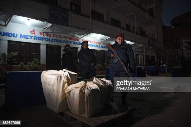 Nepali police stand guard next to sealed ballot boxes after polling stations closed in Kathmandu on December 7 2017 Nepal votes on December 7 in the...