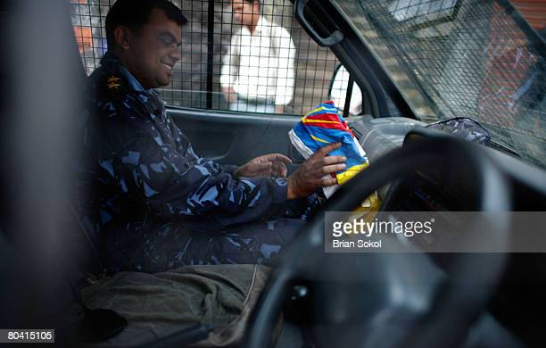 Nepali policeman laughs while stuffing a Tibetan flag wrestled away from detained Tibetan demonstrators into his vehicle's glove box during a...