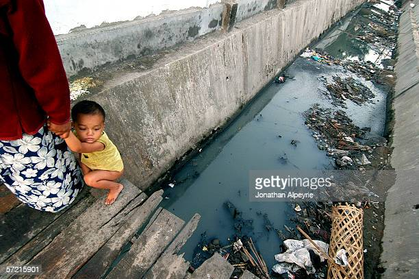 Nepali prostitute is helping her son to go the the toilet in the ditch marking the limit of the red light district November 13 2005 in Siliguri Utar...