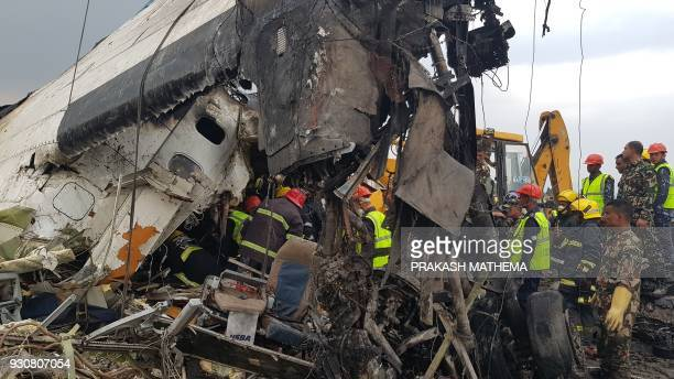 Nepali rescue workers gather around the debris of an airplane that crashed near the international airport in Kathmandu on March 12 2018 At least 40...