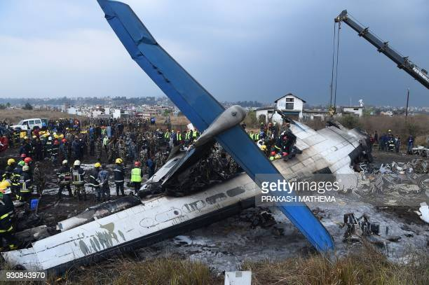 TOPSHOT Nepali rescue workers gather around the debris of an airplane that crashed near the international airport in Kathmandu on March 12 2018 At...