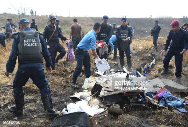 Nepali rescue workers search through the debris of an airplane that crashed near the international airport in Kathmandu on March 12 2018 At least 40...
