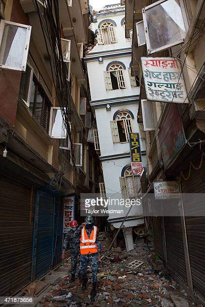 Nepali rescue workers walk beneath a building which has nearly collapsed in Kathmandu Nepal on May 1 2015 On April 25 Nepal suffered a magnitude 78...