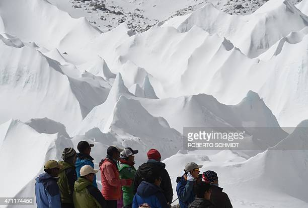 Nepali sherpas and other Nepali members of expeditons watch as an unseen rescue helicopter takes off with the injured from Everest Base Camp on April...