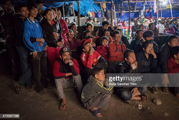 Nepali victims of the earthquake watch a movie projected onto a screen hanging from a truck on May 1 2015 in Kathmandu Nepal The road from Bahrabise...