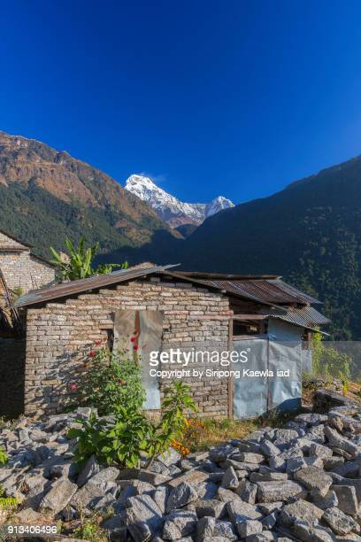 Nepali villager's house which is built with stone in Ulleri with the Annapurna South in background, Nepal.