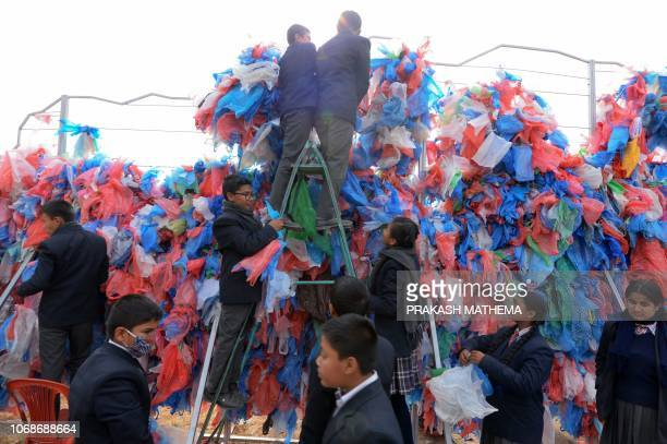 Nepali volunteers and school children tie up recycled plastic bags to make a sculpture representing the Dead Sea in a bid to set a new world record...