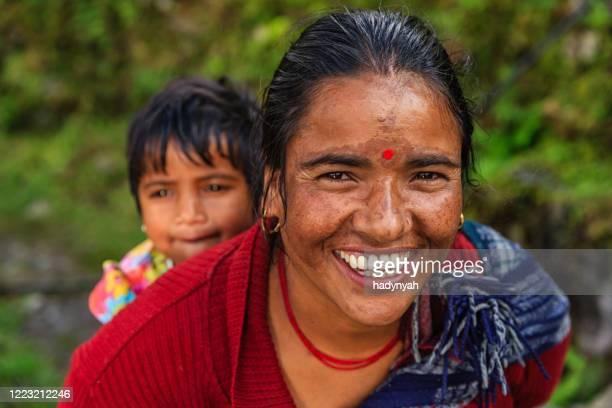 アンナプルナ山脈の近くで彼女の赤ちゃんを運ぶネパールの女性 - nepali mother ストックフォトと画像