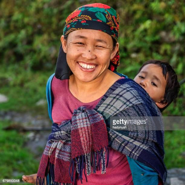 アンナプルナの範囲の近くの彼女の赤ちゃんを運んでネパールの女性 - nepali mother ストックフォトと画像