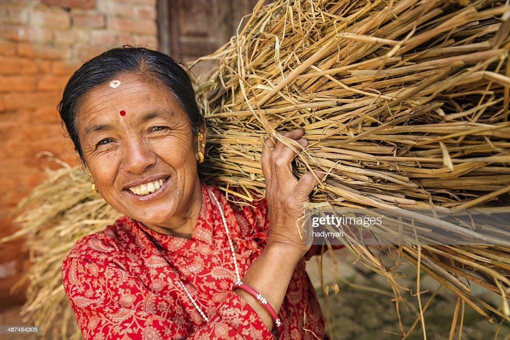 Nepali woman carrying rice straw in Bhaktapur, Nepal : Stock Photo
