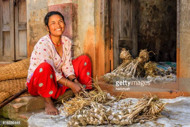 nepali woman picking over a garlic in bhaktapur, nepal - nepal stock pictures, royalty-free photos & images