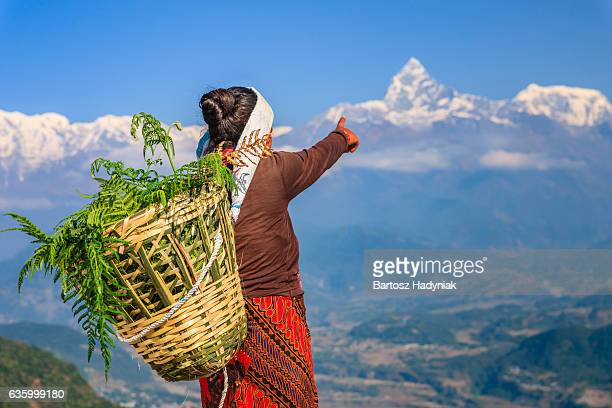 nepali woman pointing at machapuchare, pokhara, nepal - annapurna conservation area stock photos and pictures