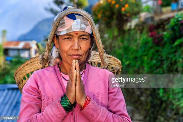 Nepali woman saying Namaste near Annapurna Range