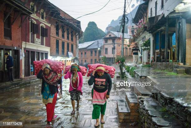 Nepali women carry bags along the street of the old town in Bandipur Nepal on March 30 2019