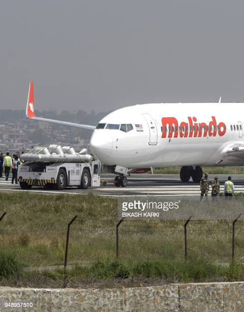 Nepali workers get a Malaysian airliner back onto the runway at the international airport in Kathmandu on April 19 after it skidded off the runway...