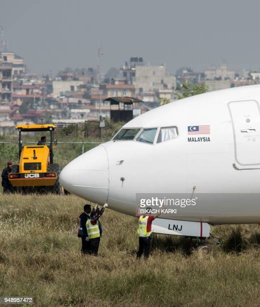Nepali workers try to bring a Malaysian airliner back onto the runway at the international airport in Kathmandu on April 19 after it skidded off the...