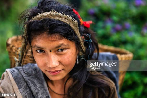 nepali young girl carrying a basket near annapurna range - nepal stock pictures, royalty-free photos & images