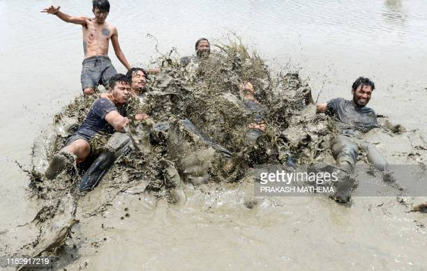 TOPSHOT Nepali youths play in the muddy water of a rice paddy field to mark National Paddy Day which celebrates the start of the annual rice planting...