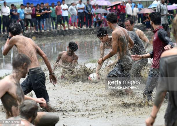 Nepali youths play with a football in the muddy water of a rice paddy field to mark National Paddy Day which celebrates the start of the annual rice...