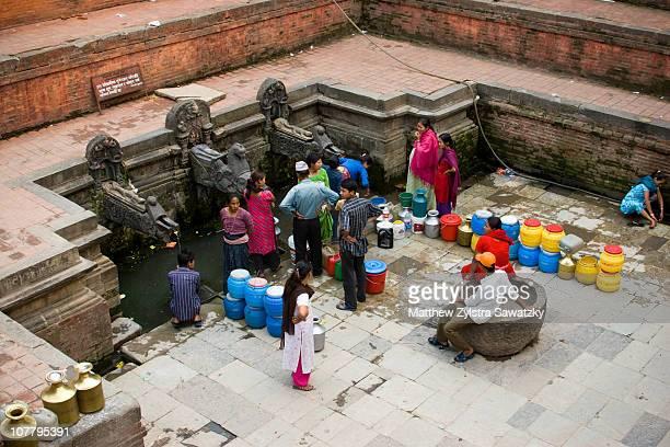 Nepalis in Kathmandu wait near the public water tap for the water to turn on.