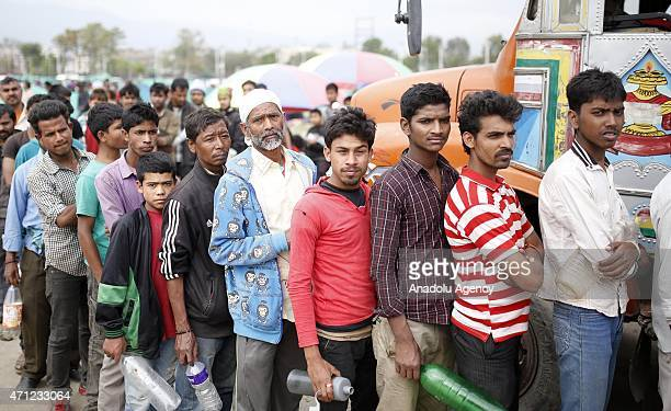 Nepalis wait in a line to fill jerry cans with water others set up tents at a empty lands in Katmandu Nepal on April 26 2015 The death toll in Nepal...