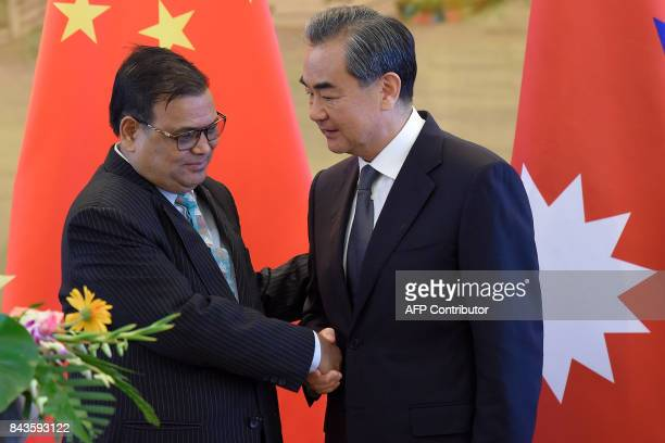 Nepal's Deputy Prime Minister Krishna Bahadur Mahara shakes hands with Chinese Foreign Minister Wang Yi at the end of a joint press conference...