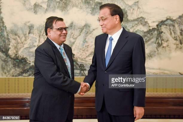 Nepal's Deputy Prime Minister Krishna Bahadur Mahara shakes hands with China's Premier Li Keqiang prior to their meeting at Zhongnanhai Leadership...