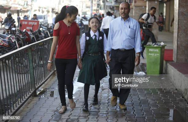 Nepal's former living goddess or Kumari Matina Shakya walks to school with her father Pratap Man Shakya and sister Mijala Shakya for the first time...