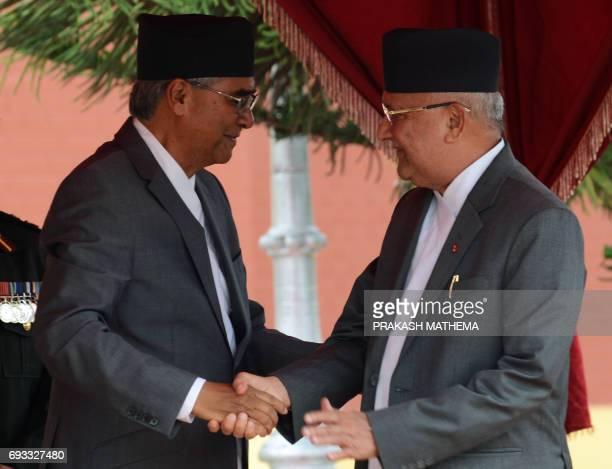 Nepal's newlyelected Prime Minister Sher Bahadur Deuba shakes hands with opposition leader Khadga Prasad Oli during Deuba's swearingin ceremony at...