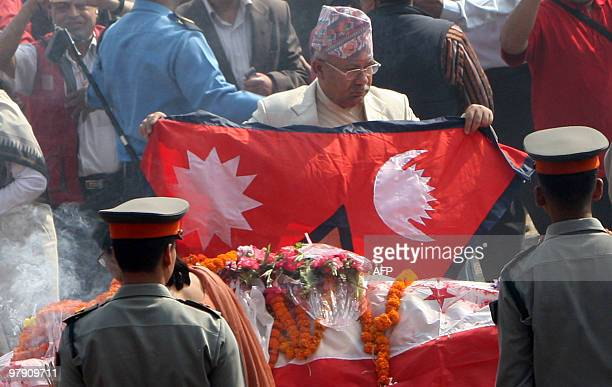 Nepal's Prime Minister Madhav Kumar Nepal lays the national flag over the body of former prime minister Girija Prasad Koirala in Kathmandu on March...