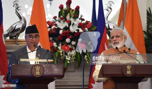 Nepal's Prime Minister Sher Bahadur Deuba listens as Indian Prime Minister Narendra Modi delivers his speech after a meeting and agreement exchange...