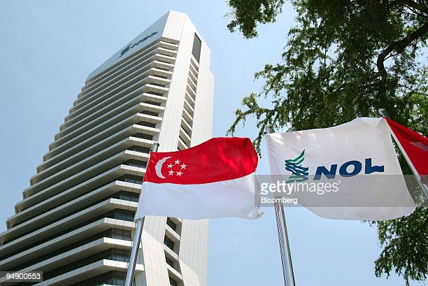 Neptune Orient Lines Ltd's flag flies next to the Singapore national flag in front of the shipping line's headquarters building in Singapore on...