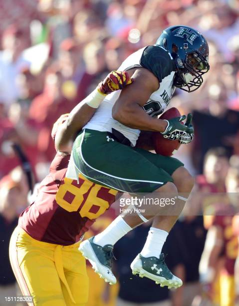 Ne'Quan Phillips of the Hawaii Warriors recovers a fumble in front of Xavier Grimble of the USC Trojans during the first half at Los Angeles Coliseum...