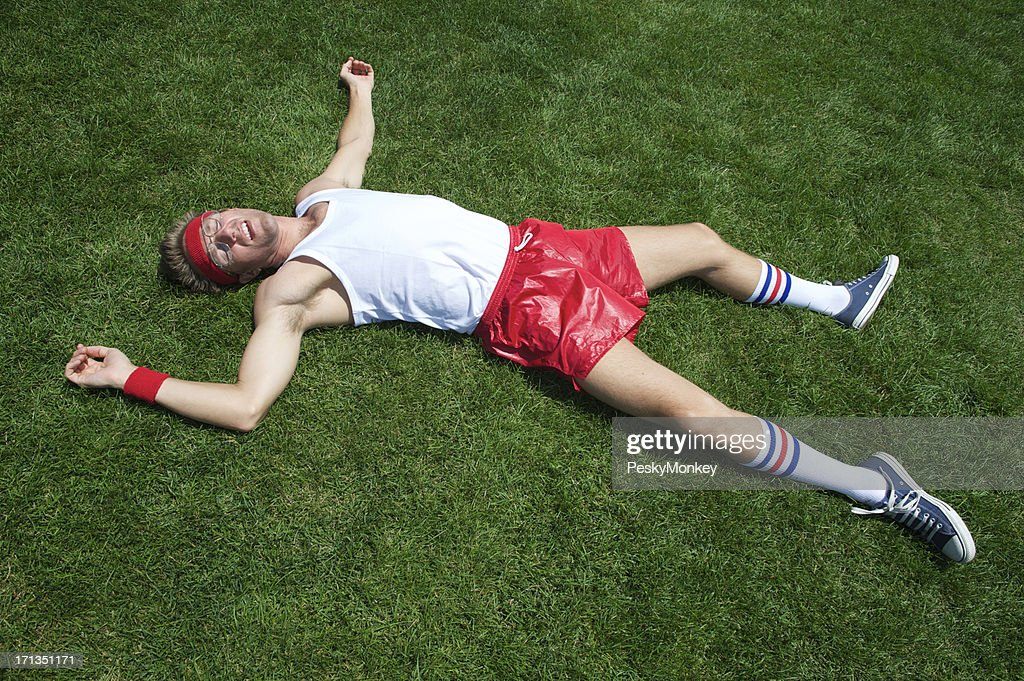 Nerd Athlete Lies Exhausted in Green Grass : Stock Photo