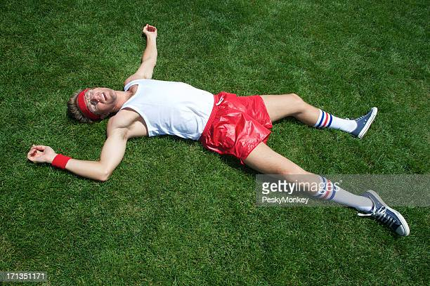 Nerd Athlete Lies Exhausted in Green Grass