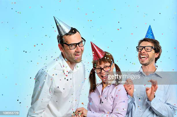 Nerd friends with party hats on head, confetti, toothy smiling