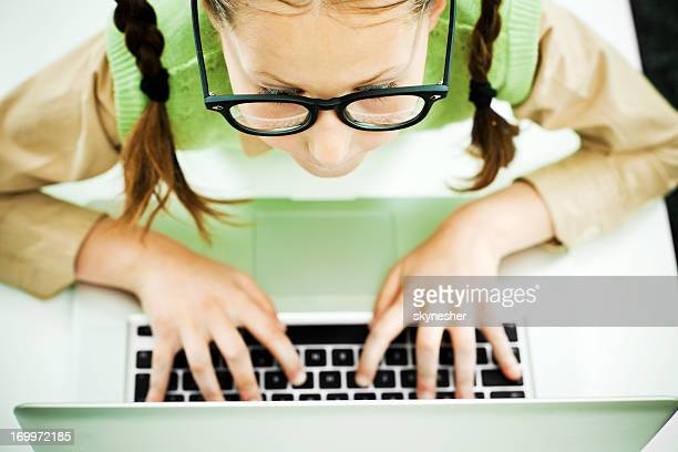 nerd girl using her laptop. - girl nerd hairstyles stock photos and pictures