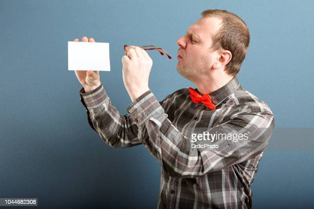nerd guy with blank card - myopia stock photos and pictures