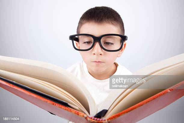 Nerd little boy with large glasses reading book