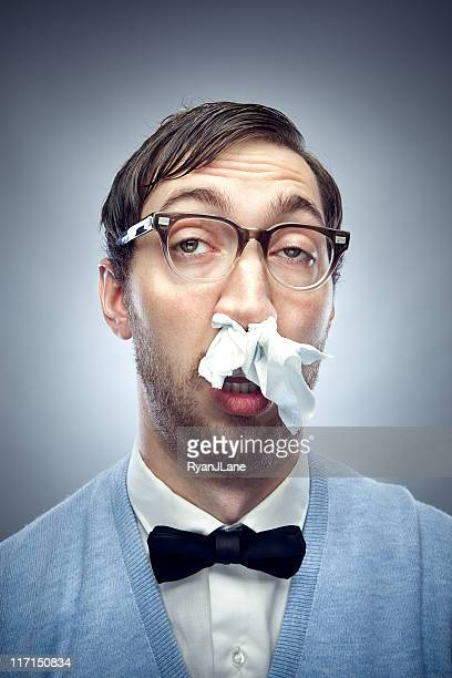 nerd with a cold and tissue in nose - cold virus stock pictures, royalty-free photos & images