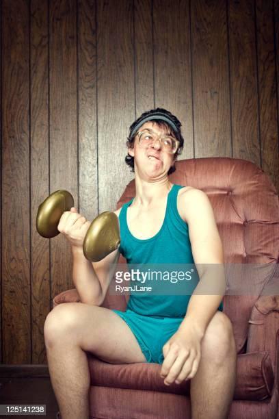 Grand dadais jeune homme faisant de l'exercice avec les poids et haltères