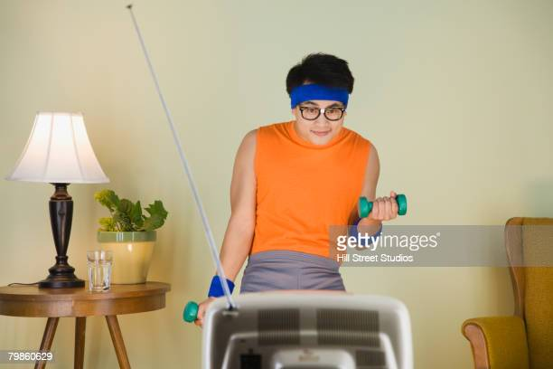 Nerdy Asian man exercising in front of television