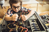 nerdy schoolboy trying to repair computer
