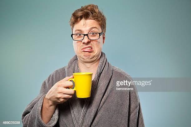 Nerdy guy in robe drinking bad coffee in a yellow mug