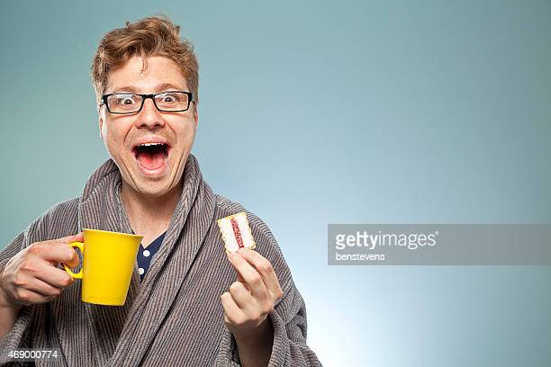 Nerdy guy smiling with a coffee and biscuit