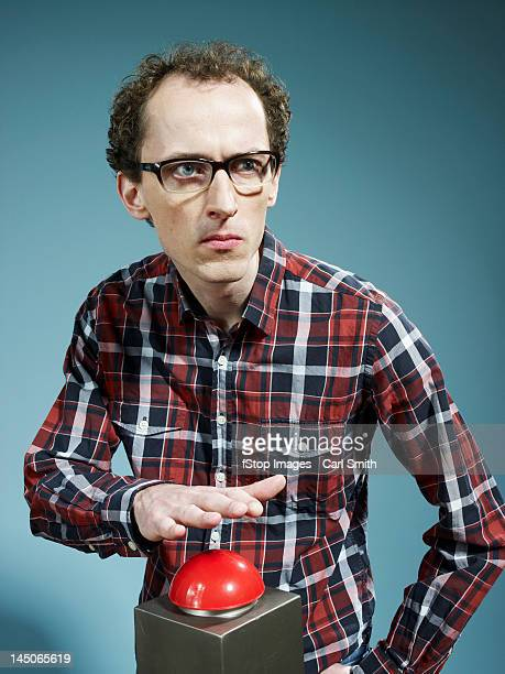 a nerdy guy with his hand poised above a red game show buzzer - nerd stock pictures, royalty-free photos & images