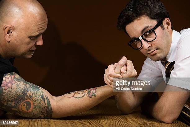 Nerdy man arm wrestling tattooed man